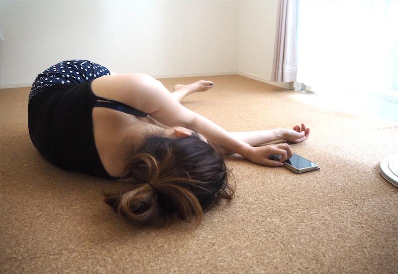 寝て電話する女性