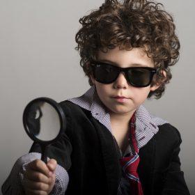 サングラスをかけて虫眼鏡で見る少年